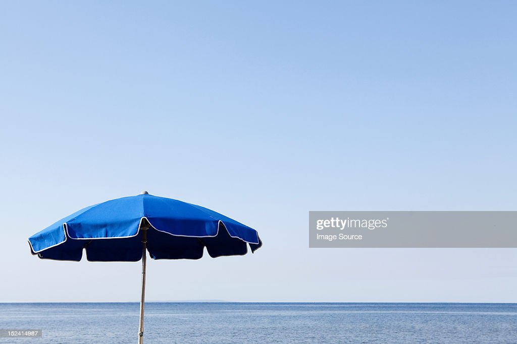 Blue parasol against the sea