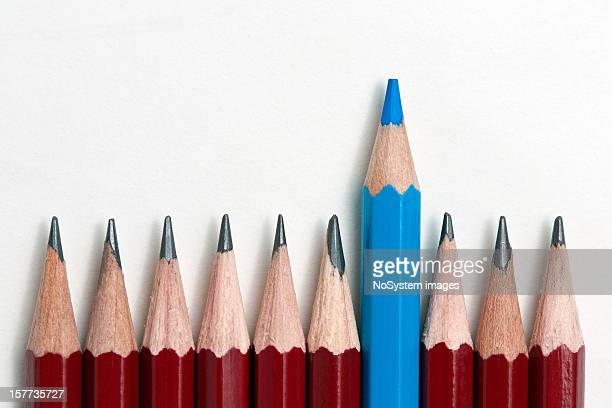 A blue pencil standing out from a row of red pencils