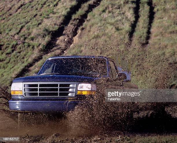 Blue pick up truck driving through a mud puddle