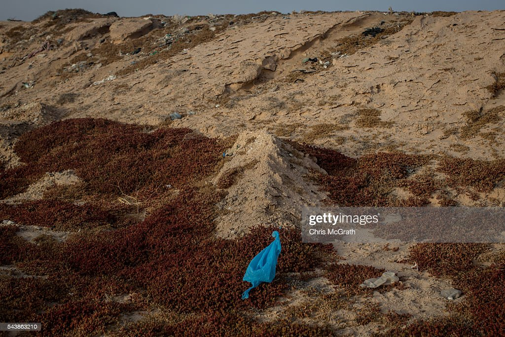 A blue plastic bag marks the grave of a migrant in a makeshift graveyard on the edges of a salt flat on June 30, 2016 in Zarzis, Tunisia. The makeshift cemetary has an estimated 30 migrants buried in unmarked graves. Since 2012, the Tunisian border town of Zarzis has dealt with the overflow of migrants from Libya. In 2015 with pressure from EU nations, Tunisia tightened its border security with Libya, cutting the number of migrants arriving in Tunisian border towns. Local fishermen from the Zarzis port who were trained in rescue techniques by MSF in 2015 after being involved in weekly rescues, have seen no rescues so far in 2016, primarily due to an increase in rescue boats from international NGOÕs, coastguards and military vessels patrolling the waters off the Libyan coast. However with an estimated 800,000 migrants waiting in Libya to attempt the dangerous crossing to Europe, preparations were made for an expected increase in rescues and arrivals to Tunisia ahead of the 2016 peak season