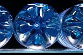 Bouteilles en plastique avec l'eau bleue sur un réfrigérateur intégré