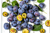blue plums on light wooden background.fruits.the view from the top