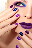 Blue purple fashion multicolored manicure and makeup on a woman in close-up.