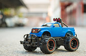 Blue RC truck car (Radio-controlled car) on the asphalt ground. Off road car. This toy have some dust from children playing.