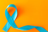 Blue ribbon.  Isolated on orange background with empty space for text .