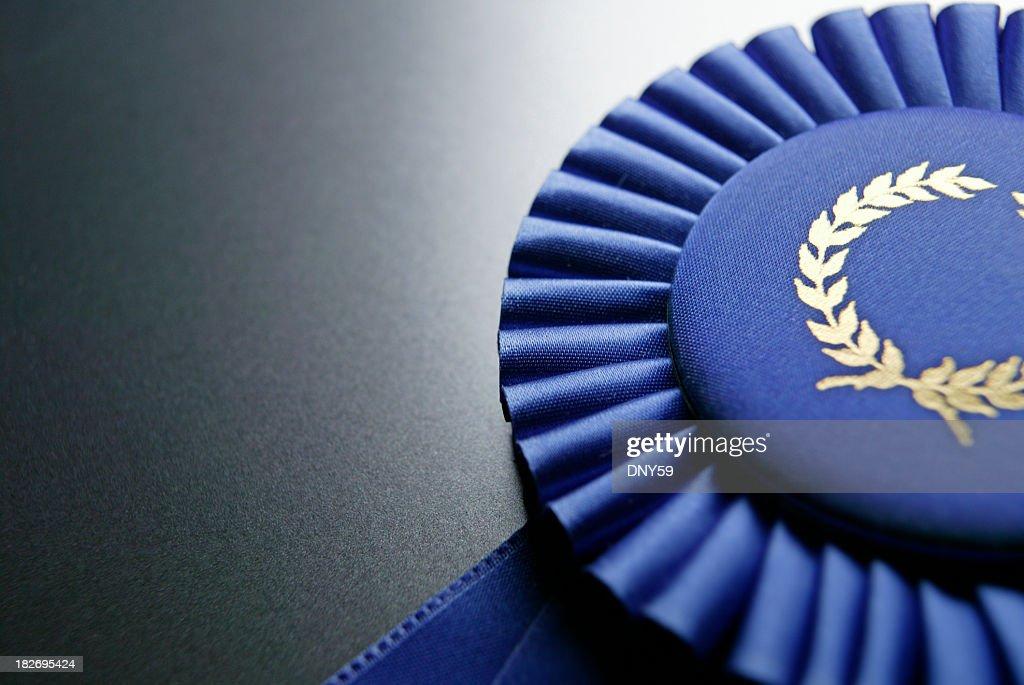 Blue ribbon rosette on dark gray graduated background