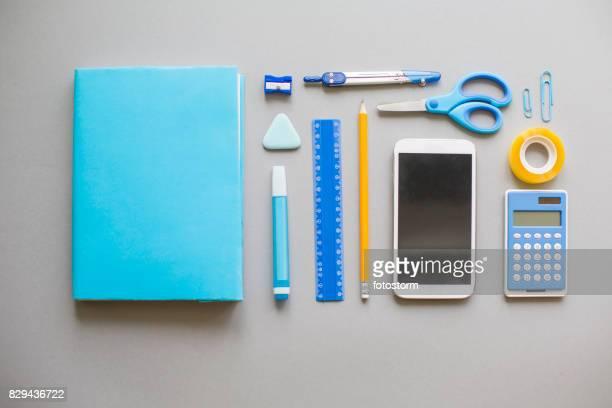 Blue school supplies on grey background