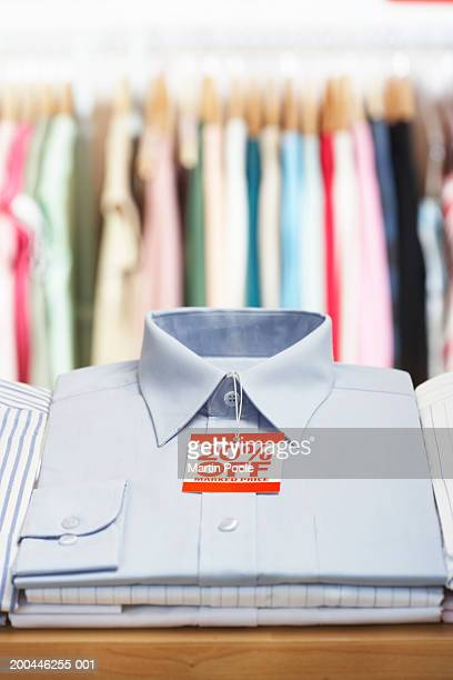 Blue shirt with discount tag attached on shop display, close-up