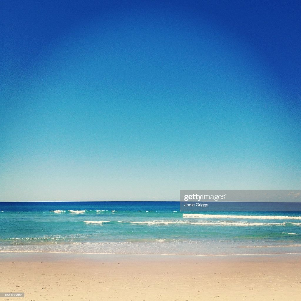 Blue skies over aqua ocean waters at beach