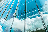 blue sky and clouds reflected at glass wall.