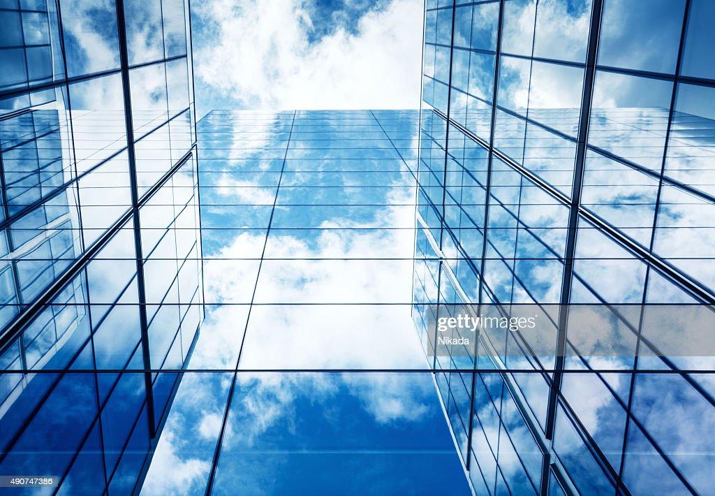 Cielo blu e nuvole che riflette nell'architettura in vetro moderno : Foto stock