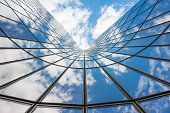 Blue sky and white clouds reflecting in a curved glass building