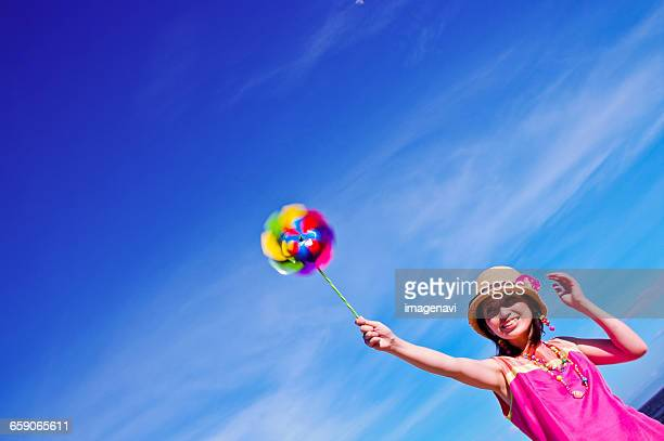 Blue sky and woman with pinwheel