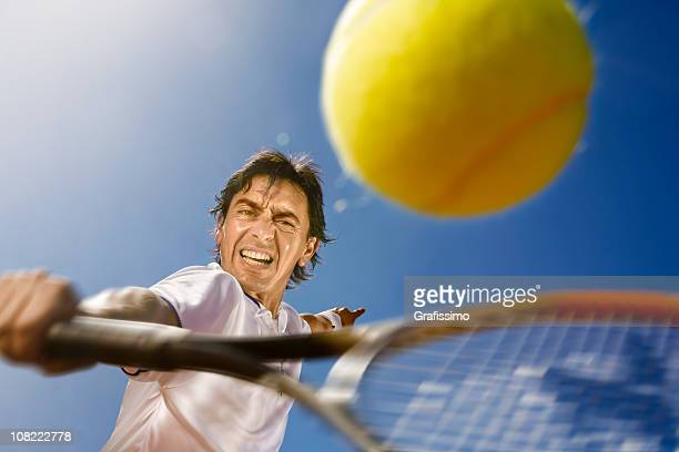 Blue sky over tennis player hitting the ball