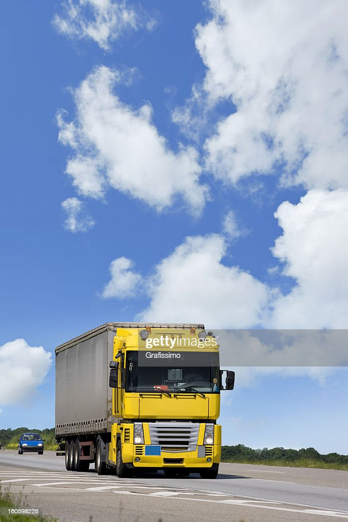 Blue sky over yellow truck on a highway : Stock Photo