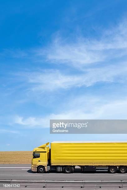 Blauer Himmel über Gelbes Lkw auf der Autobahn