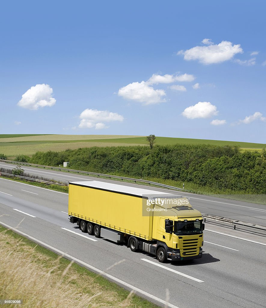 Blue sky over yellow truck on a highway