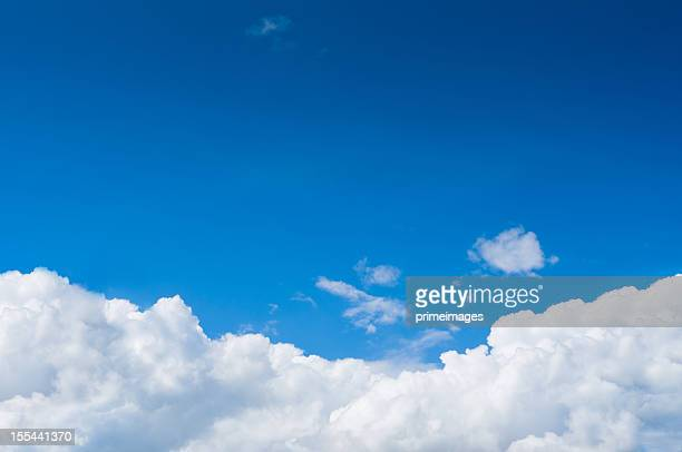 Blue sky with dramatic white clouds below