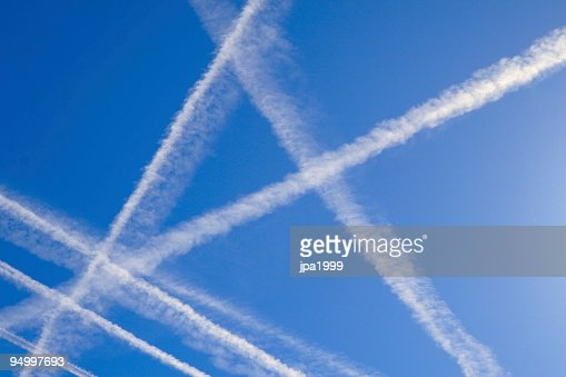 A blue sky with plane trails crossing over each other