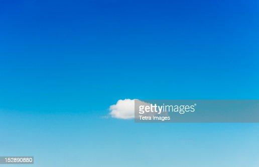 Blue sky with single cloud