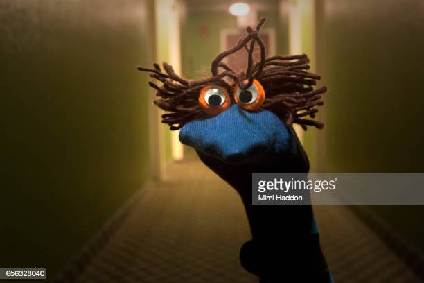 Blue Sock Puppet with Brown Hair in Long Corridor