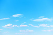 Pastel blue spring sky with white light clouds. Background with space for your own text