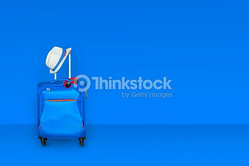 Blue suitcase with a summer hat and fashionable  sunglasses on light blue background, a summer vacation travel concept, free space with a place for copying, 3d rendering : Stock Photo