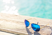 Blue Sunglasses on wooden decking by seaside