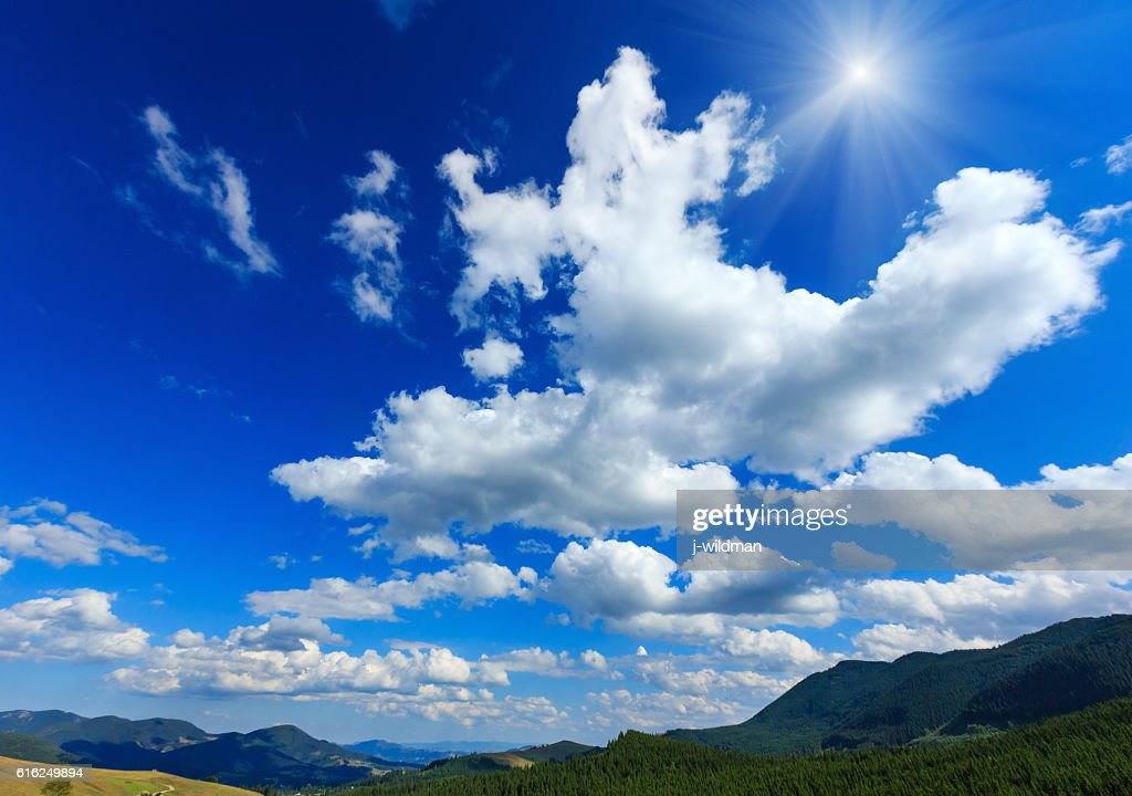 Blue sunshiny sky with white clouds over mountain. : Stock-Foto