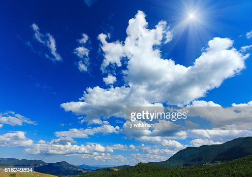 Blue sunshiny sky with white clouds over mountain. : Foto de stock
