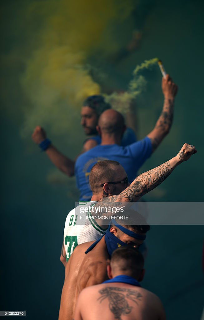 Blue team supporters cheer their side against white during the final match of the calcio storico fiorentino traditional XVI century ball game in Florence Piazza Santa Croce on June 24, 2016. / AFP / FILIPPO