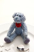 A blue teddy bear sitting on a plate with decorative stars and a spoon