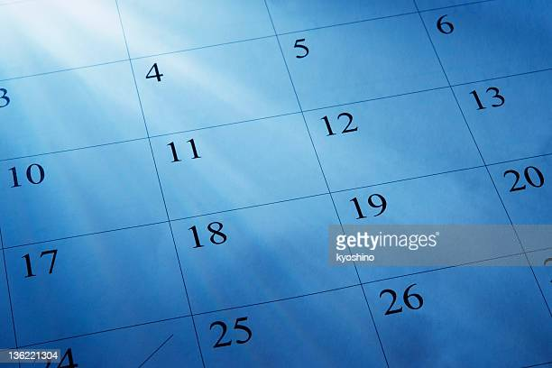 Blue tinted image of light rays and a calendars
