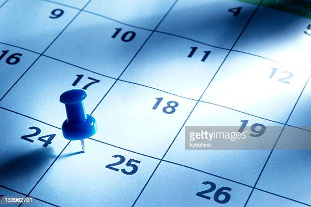Blue tinted image of thumbtack in calendar with light rays