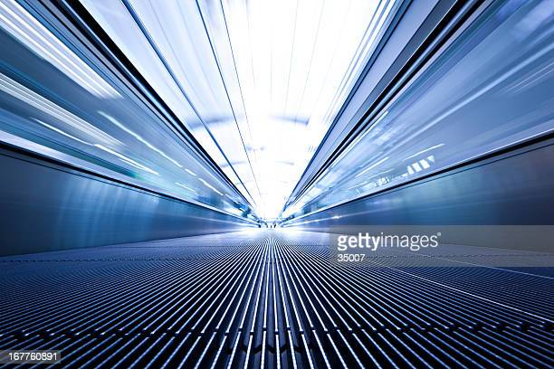 Blue toned low angle photo of moving walkway