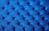 Navy blue velvet capitone textile background, retro Chesterfield style checkered soft tufted fabric furniture diamond pattern decoration with buttons, close up
