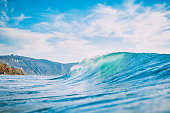 Blue wave in ocean. Barrel wave for surfing, sun light and shore