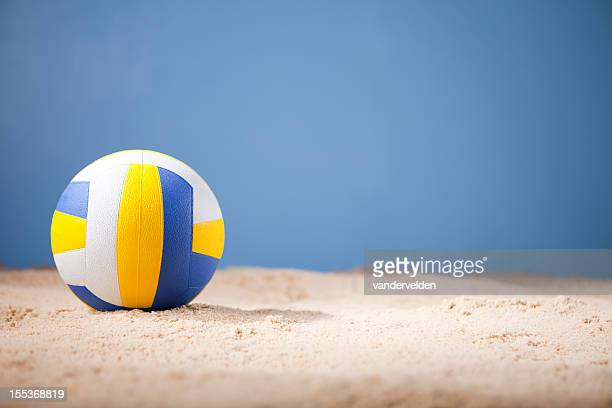 Blue white and yellow volleyball on beach with copy space
