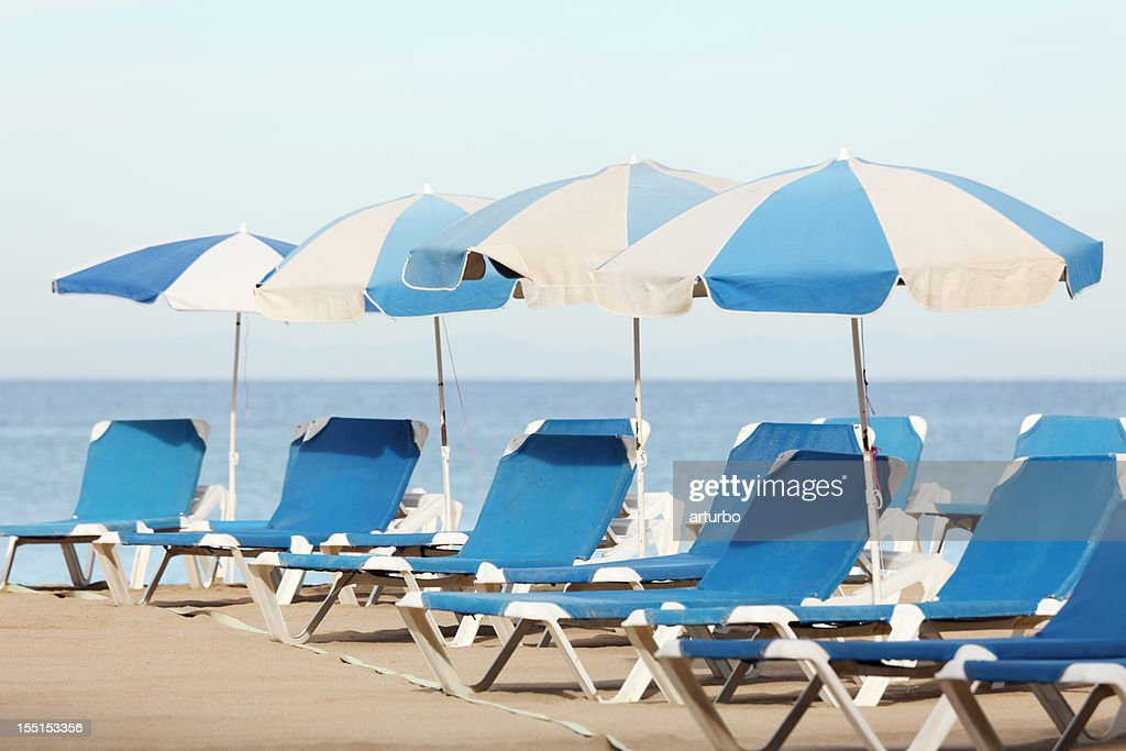 blue white sun umbrellas and sunbeds at the beach