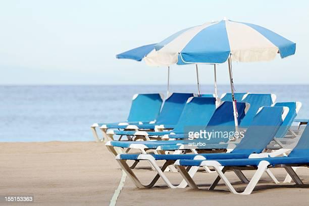 Azul y blanco sol sombrillas y sillas reclinables en la playa