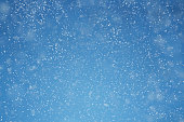 Falling snow over blue background with copy space