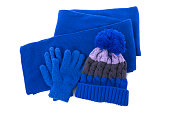 Blue winter knitted bobble hat, scarf gloves isolated