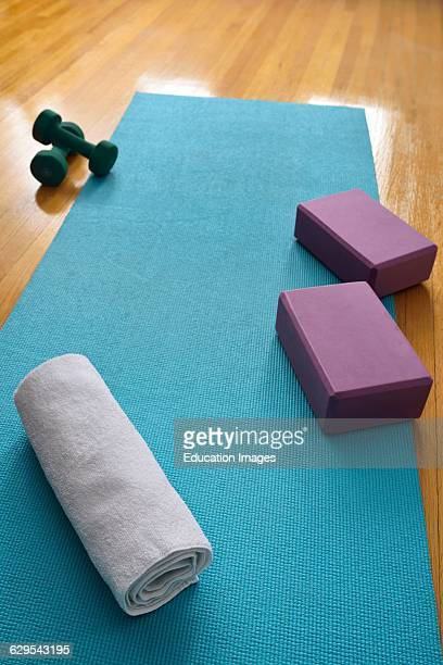 Blue yoga mat in gym studio with oak floor and towel barbells and blocks