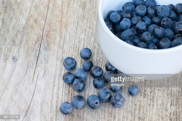 Blueberries and bowl on old wood