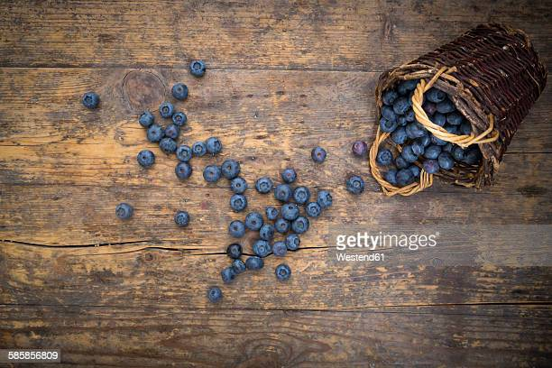 Blueberries and wickerbasket on wood