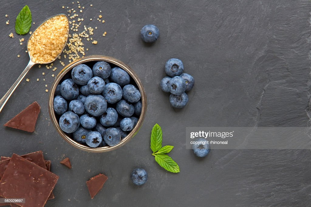 Blueberries, chocolate and mint on a slate