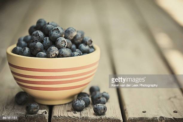 Blueberries in bowl on wood deck