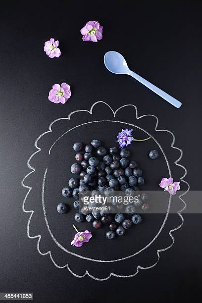 Blueberries on plate painted with chalk, close up