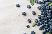 Freshly picked blueberries spilled on the wooden background with copy space