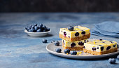 Blueberry bars, cake, cheesecake on a grey plate on blue stone background.
